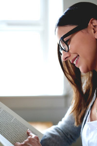 Woman sitting at desk reading a book