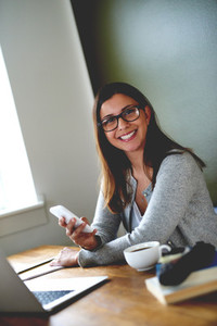 Woman sitting in home office smiling and holding mobile phone