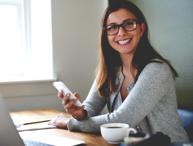 Woman smiling sitting at desk in home office