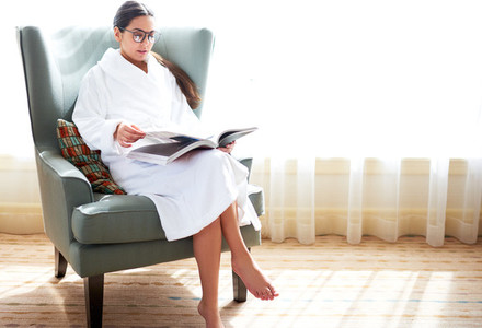 Woman sitting in chair reading book