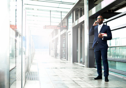 Businessman Standing at Walkway Calling on Phone