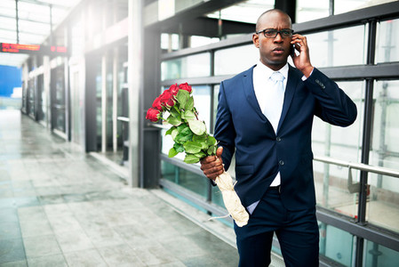 Businessman with Flowers Calling on his Phone