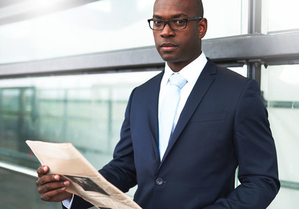 Businessman with Newspaper Looking at Camera