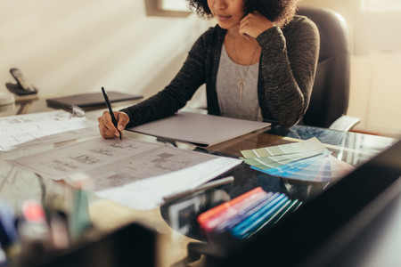 Female architect working new designs at her work desk