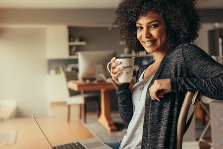African woman taking coffee break while working from home