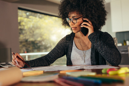 Businesswoman talking on smartphone and working in office