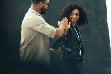 Photographer giving a high five to a female model during a photo