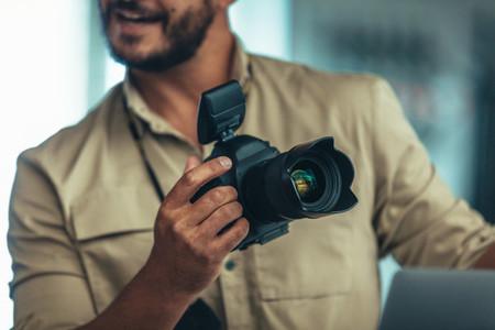 Close up of man holding a digital camera