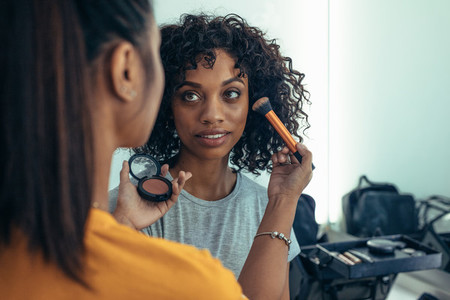 Makeup artist working on face of a model