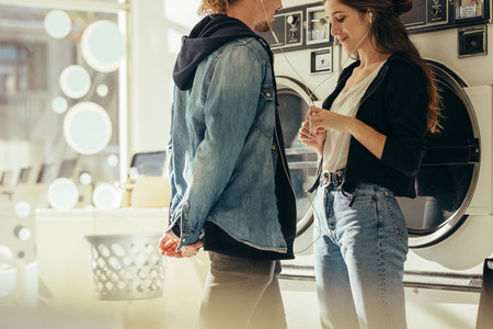 Smiling couple listening to music standing in a laundry room