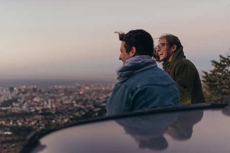 Smiling couple on a hilltop looking at the city below