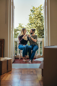 Couple sitting in balcony toasting their glasses on wine