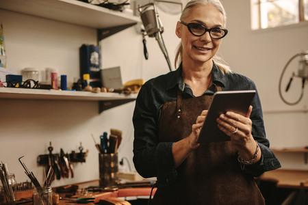 Jewelry maker using digital tablet in her workshop