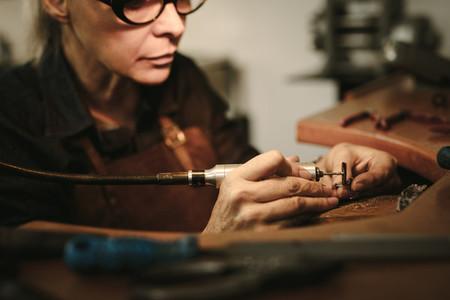 Goldsmith polishing a jewelry