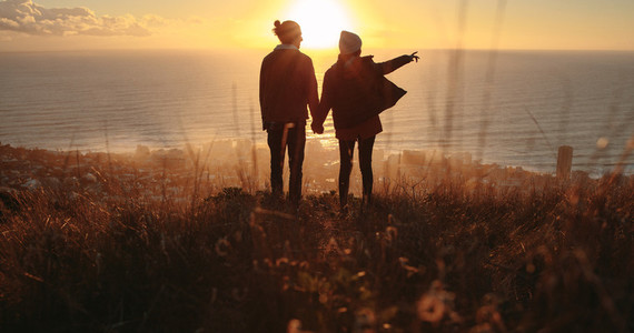 Traveling couple overlooking the seascape during sunset
