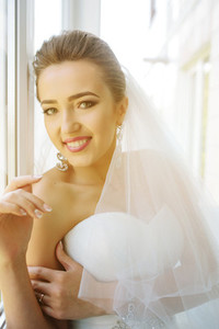 Young beautiful bride posing against the window