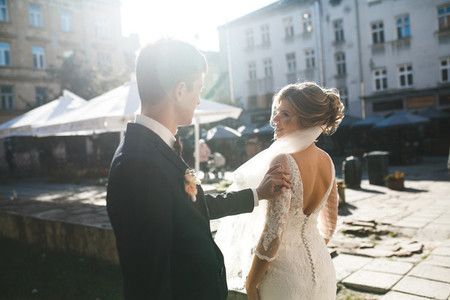 bride and groom posing on the streets