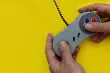 Man playing video game with controller yellow background