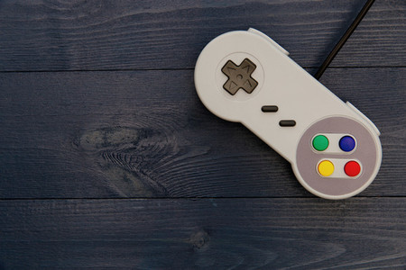 Retro video game controller on dark table background