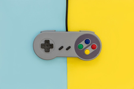 Retro video game controller yellow blue background
