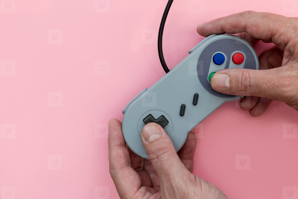 Man playing video game with controller pink background