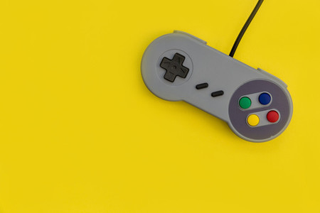 Retro video game controller yellow background copy space