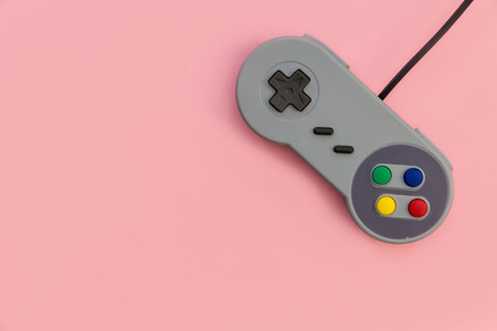 Retro video game controller pink background