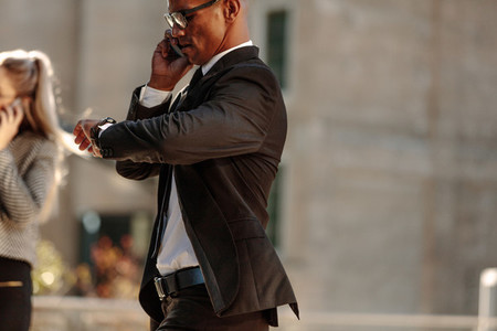 Businessman checking time while going to office