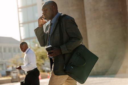 People busy using mobile phone while walking on street to office