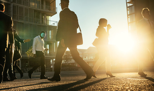 Business people walking on a busy street early in the morning