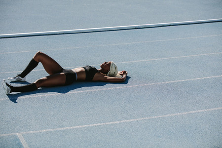 Woman athlete relaxing on running track after training