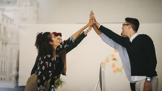 Business colleagues giving high five and celebrating in office
