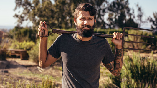 Beard man with pitchfork on farm