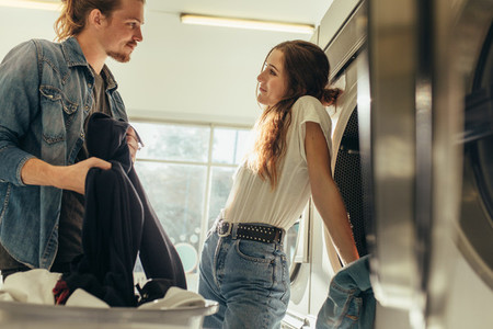 Couple in love standing together in a laundry room