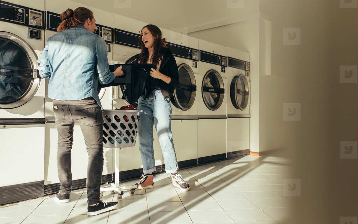 Happy couple washing clothes together in a laundry room