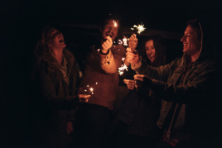 Group of friends lighting fire sparkles