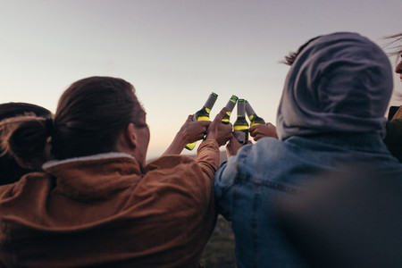 Friends toasting bottles of beer outdoors
