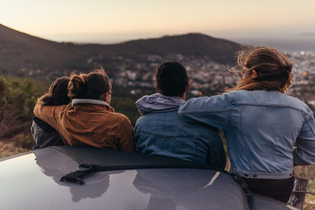 Friends looking at the city from a road on top of a hill