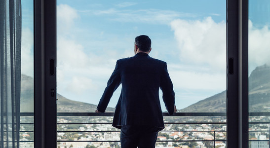 Businessman standing by hotel room balcony