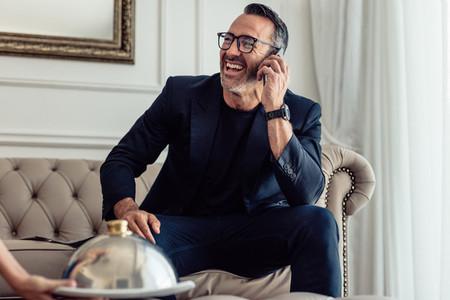 Cheerful businessman talking on mobile phone in hotel room