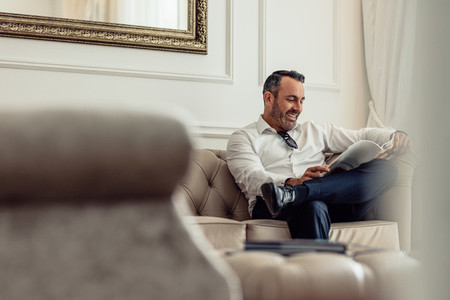 Businessman reading a magazine in hotel room