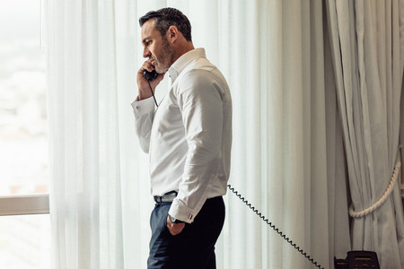 Businessman making call from hotel room