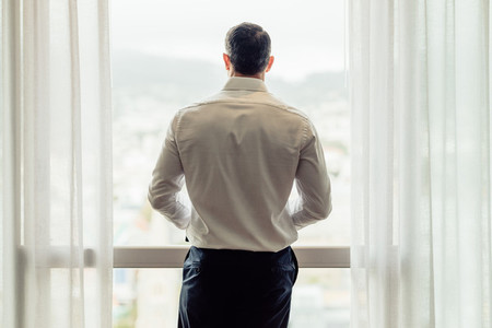 Businessman standing at hotel room window