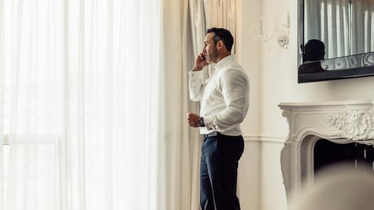 Businessman speaking on mobile phone in hotel room