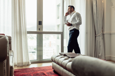 Businessman making phone call from hotel room