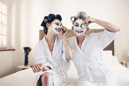 Happy women sitting on bed in bathrobes putting on beauty face m