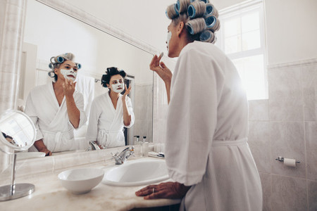 Women applying face cream standing before the mirror