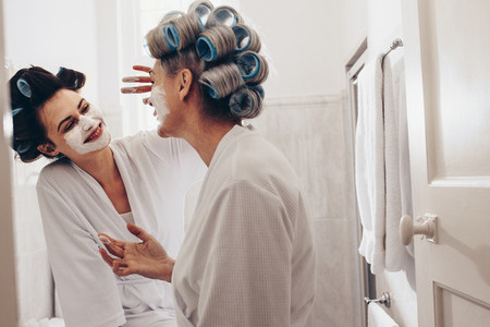 Smiling woman applying face cream to her mother