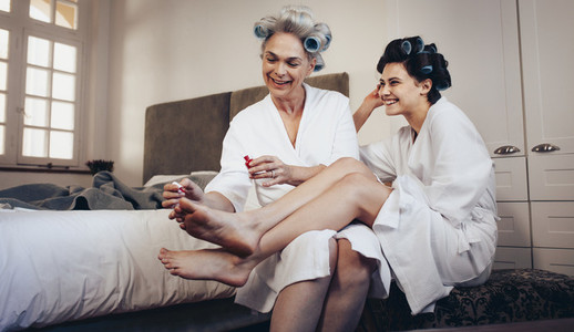 Mother and daughter grooming at home doing pedicure