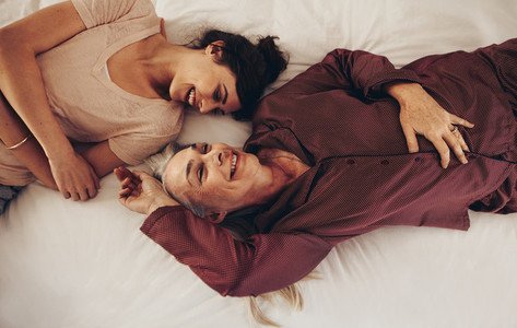 Top view of smiling mother and daughter lying on bed facing each